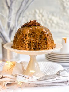 Steamed ginger and date pudding drizzled with toffee sauce and decorated with star anise on a cake stand
